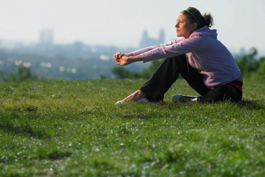 woman sits in grass taking time for self kindness