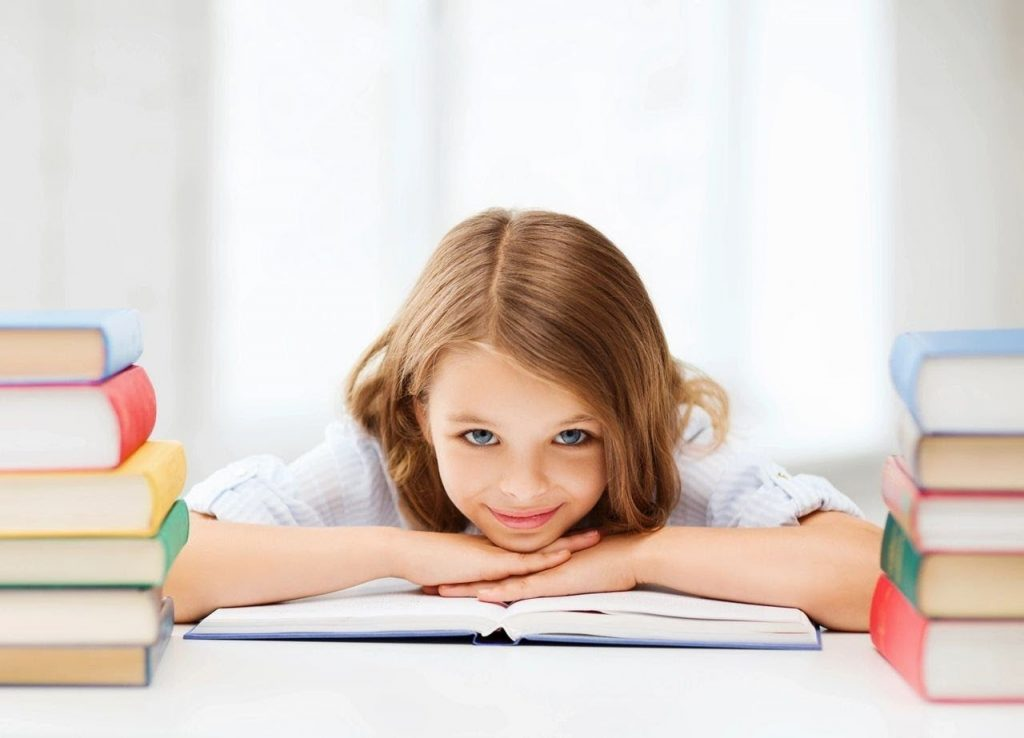 young school girl with books stacked around here smiles at the camera wondering is homeschool better than distance learning