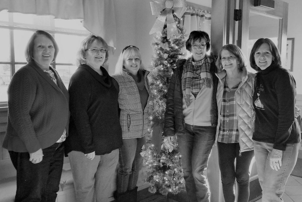 six female friends standing around a christmas tree