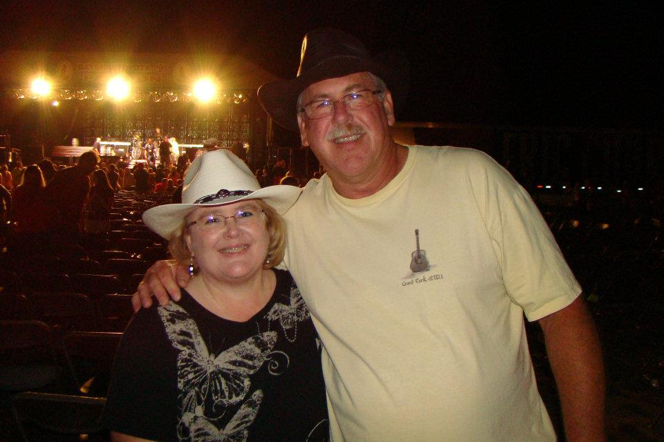 man and woman attend a country music concert wearing western hats