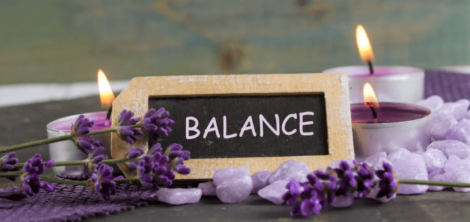 finding balance sign with purple flowers and candles