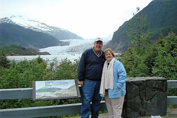 man and woman standing at an overlook in front of Mendenhall Glacier in Alaska
