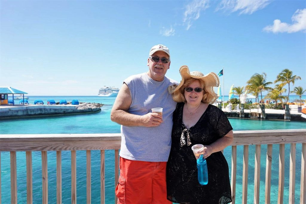 man and woman standing on a bridge overlooking the Caribbean sea with a cruise ship in the background