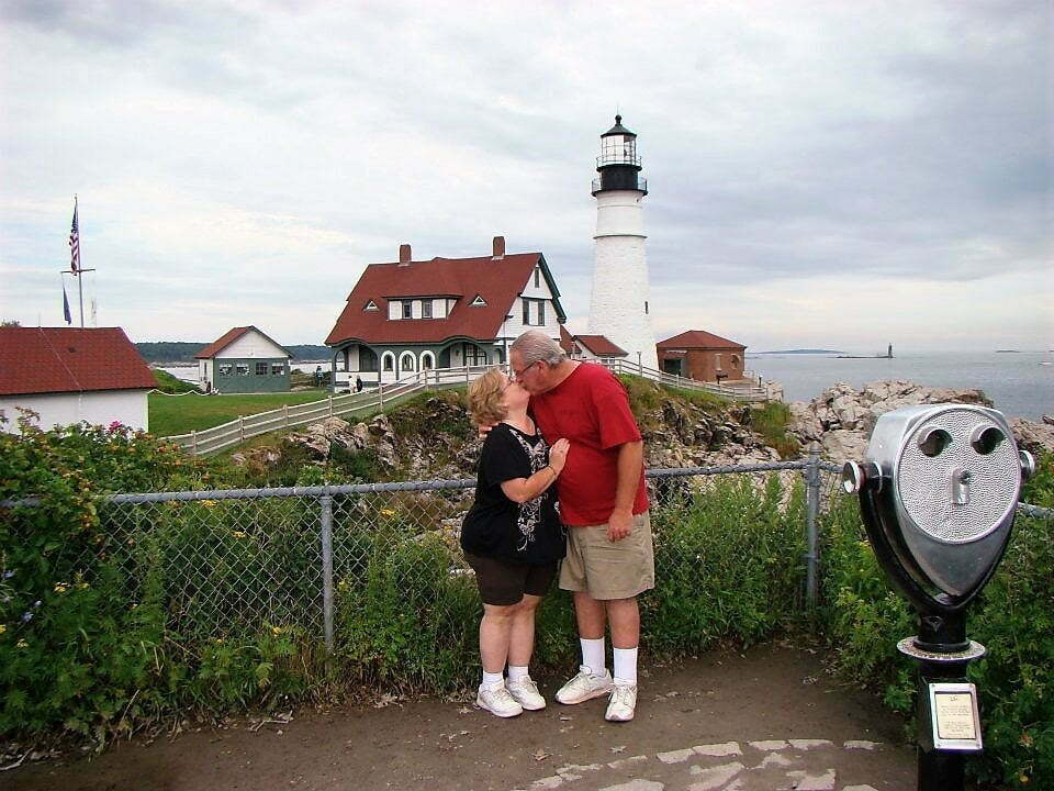 man and woman kissing with portland light house in the background