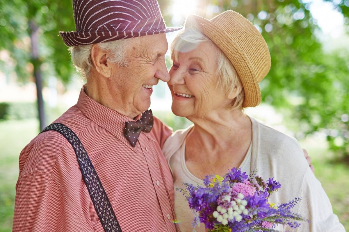 elderly couple hugging in a garden looking lovingly into each others eyes