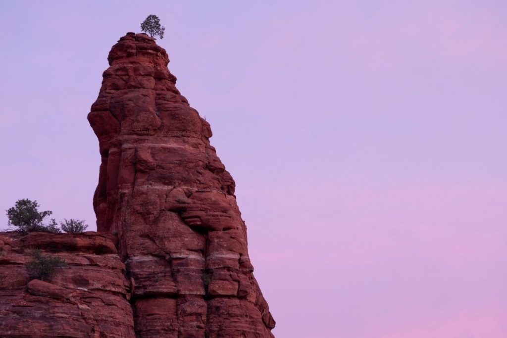 large red rocks with trees on top and sky in the background