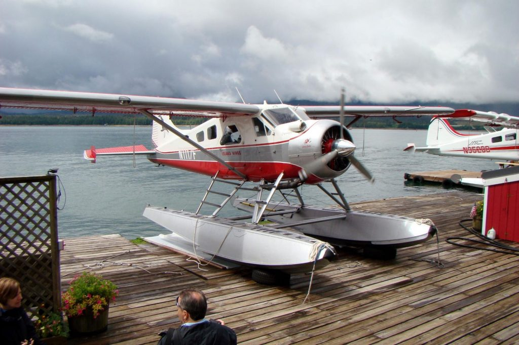 alaskan float plane red and white sitting on a platform ready to load riders