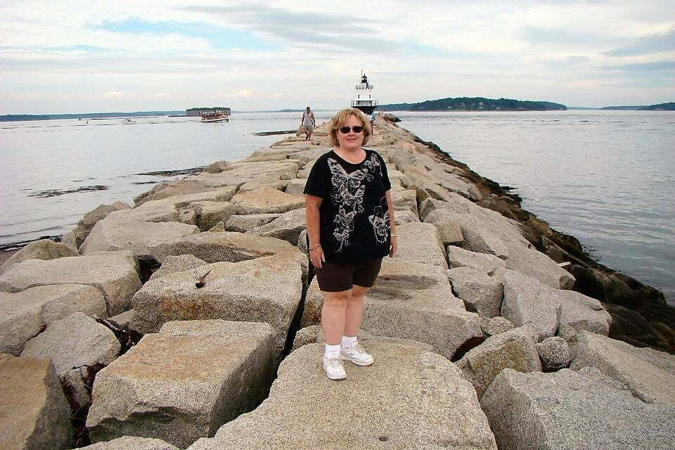woman standing on boulder walkway in water to get to lighthouse