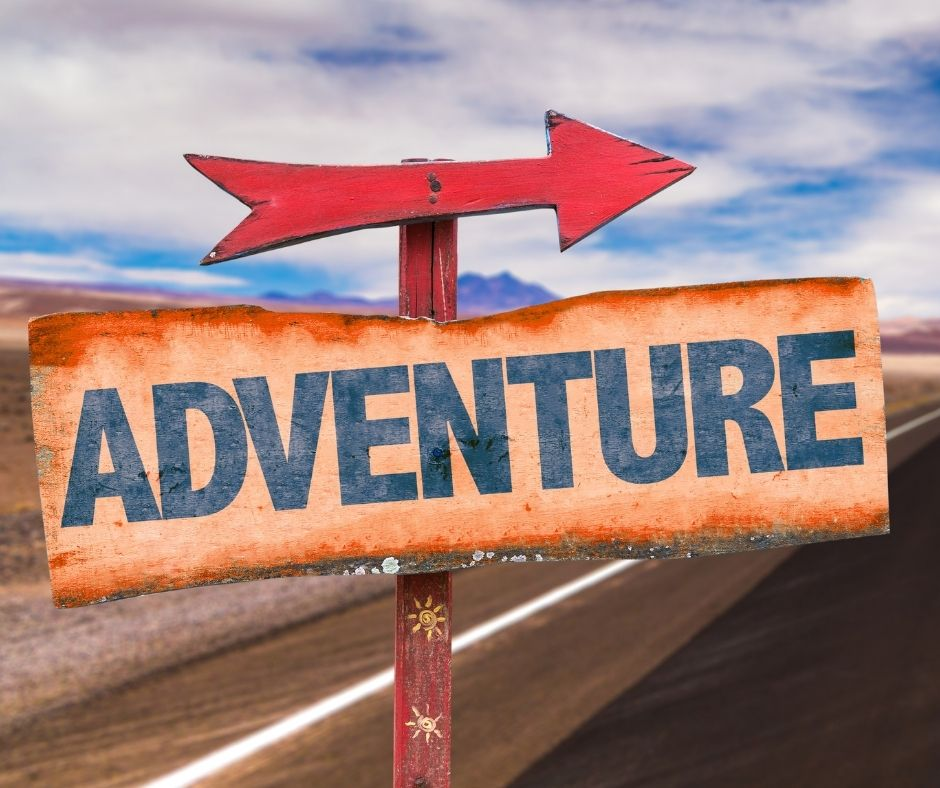 wooden adventure sign and red arrow on the side of the road showing us off on our next adventure