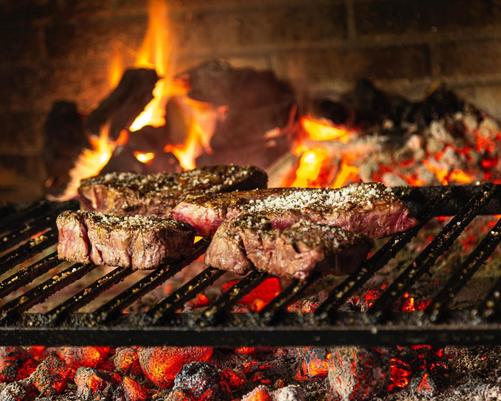meat cooking in an open flame bbq pit