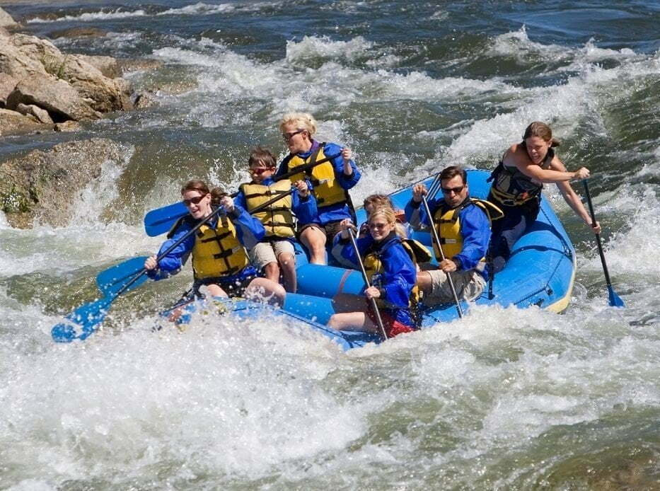people white water rafting in a large blue raft