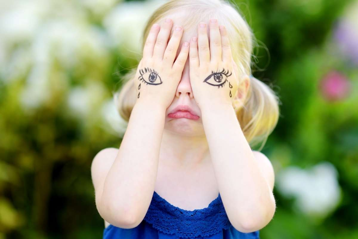 little girl with hands over her eyes pouting and tears drawn on her hands like she is having a mental health breakdown
