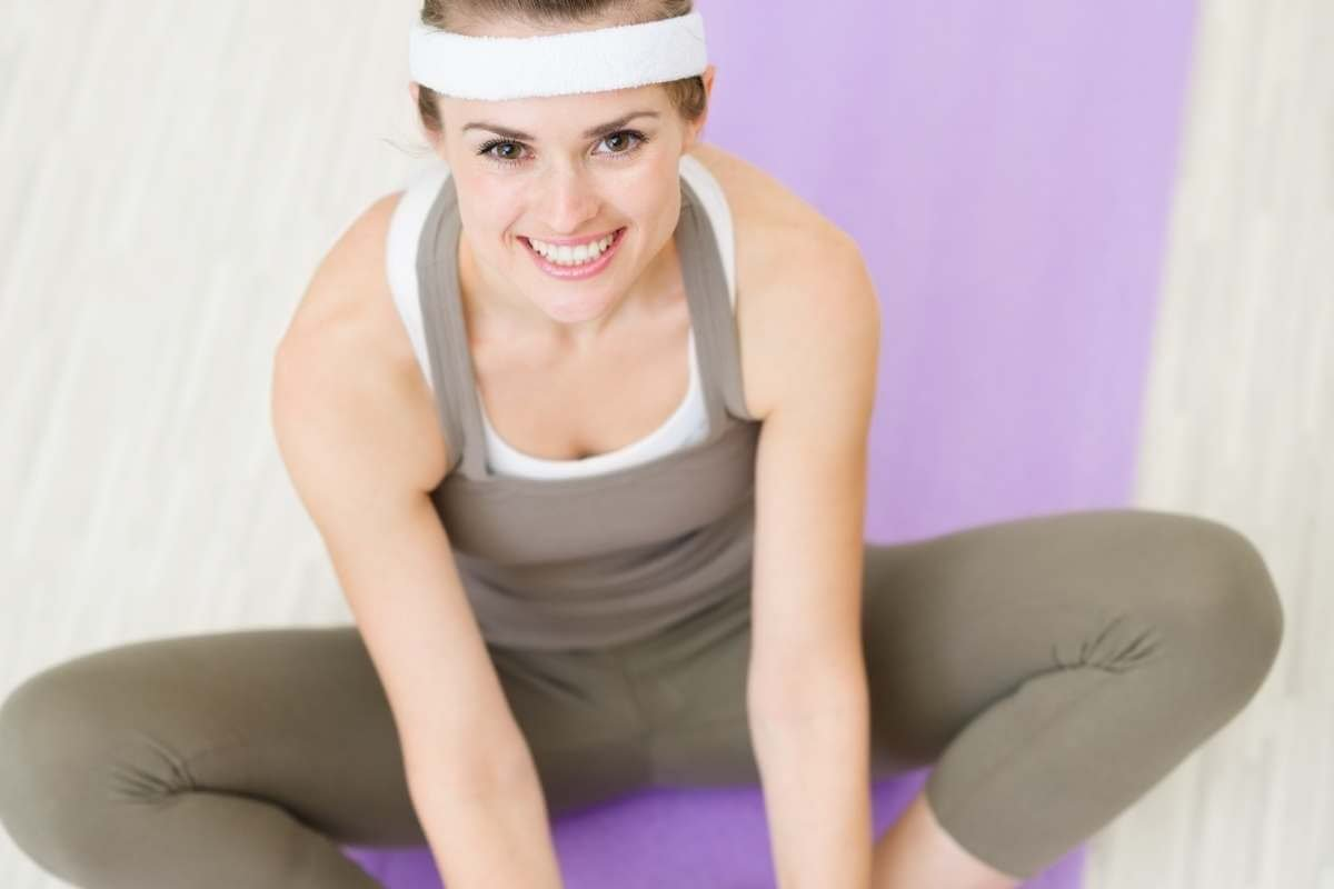 young woman doing yoga on lavender yoga mat for physical and mental health