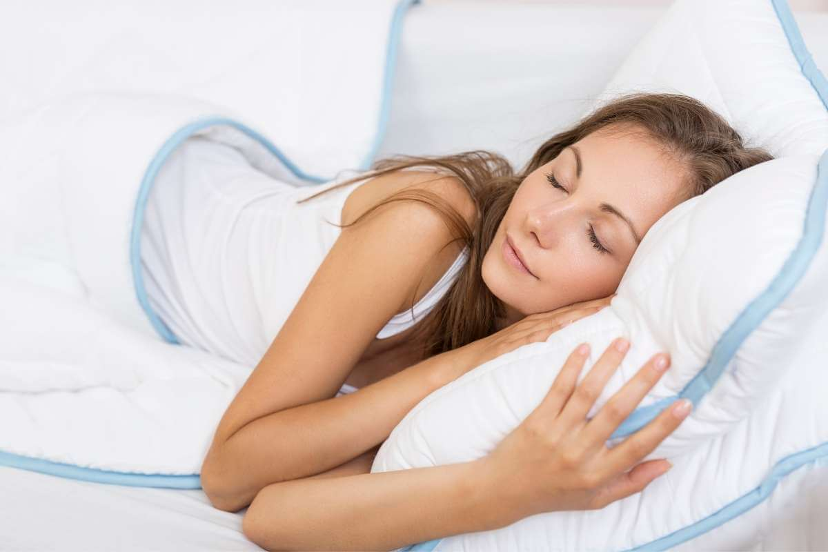 young women sleeping on white sheets showing habits to improve mental health