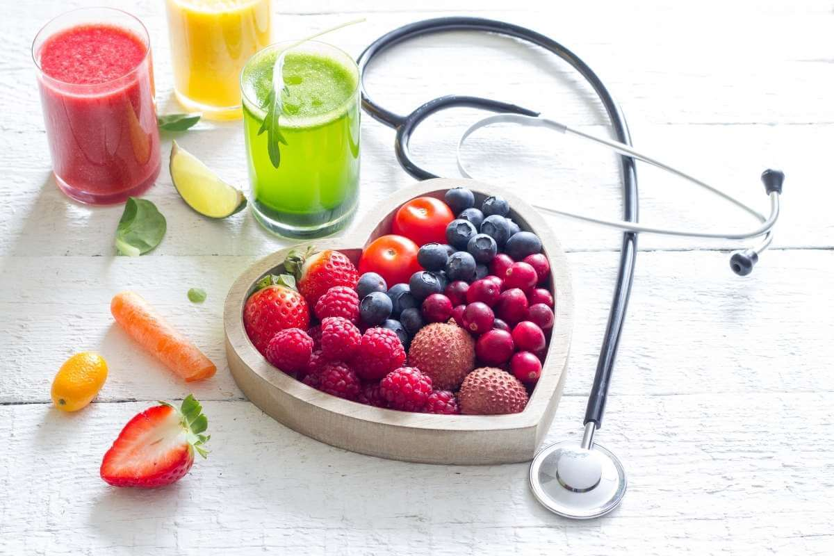 heart shaped dish with fresh fruits 3 glasses of juices and a stethoscope