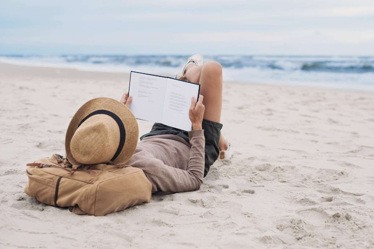 women laying on beach reading a book peacefully showing habits to  improve mental health