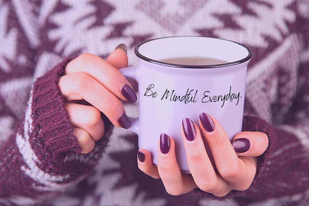 a women with purple nails wearing a cozy purple and white sweater holding a mug that says be mindful everyday