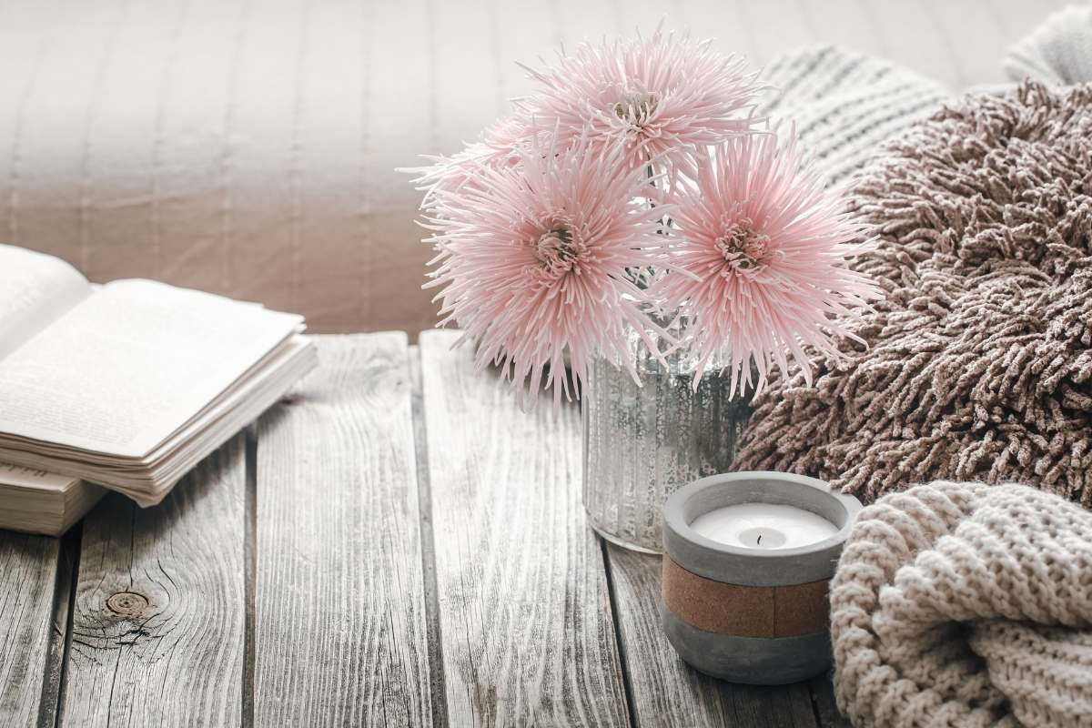 pale pink flowers candle and a book sitting on a wooden table