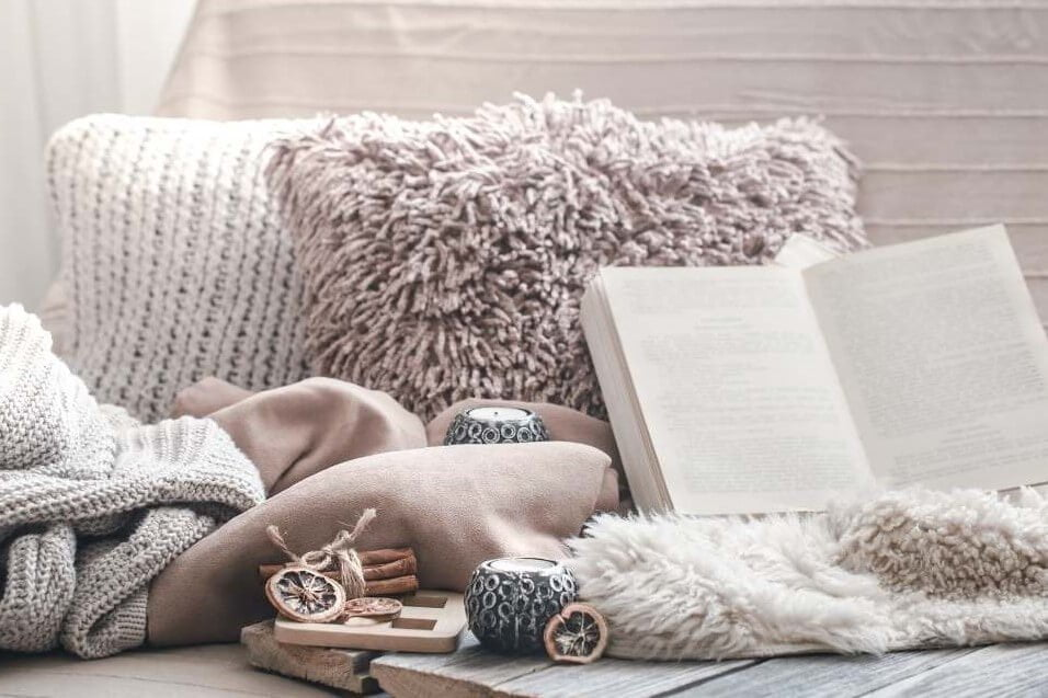 a cozy nook with a book pillows candles blankets in neutral cream colors depicts how to bring more cozy into your life