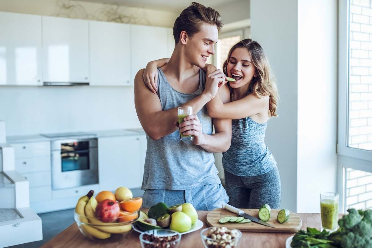 a man and woman in a kitchen cutting fruits and vegetables together