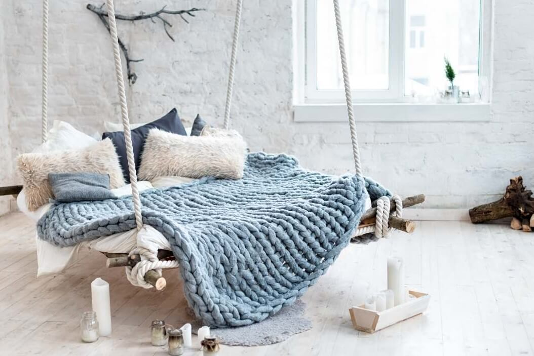 a large multi person hammock with a blue afghan blue pillows white pillows candles sitting on the floor and natural wood decor around it