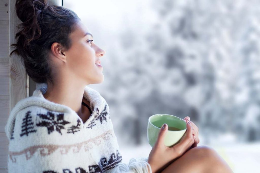 a woman wearing a cozy sweater sits on a window ledge looking outside the window smiling with a mug in her hands