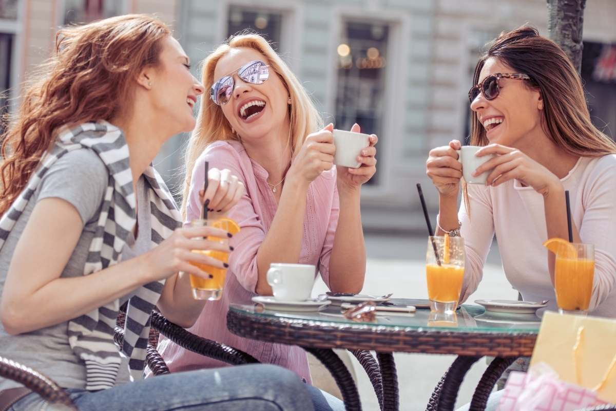 3 female friends sit at an outdoor cafe laughing together