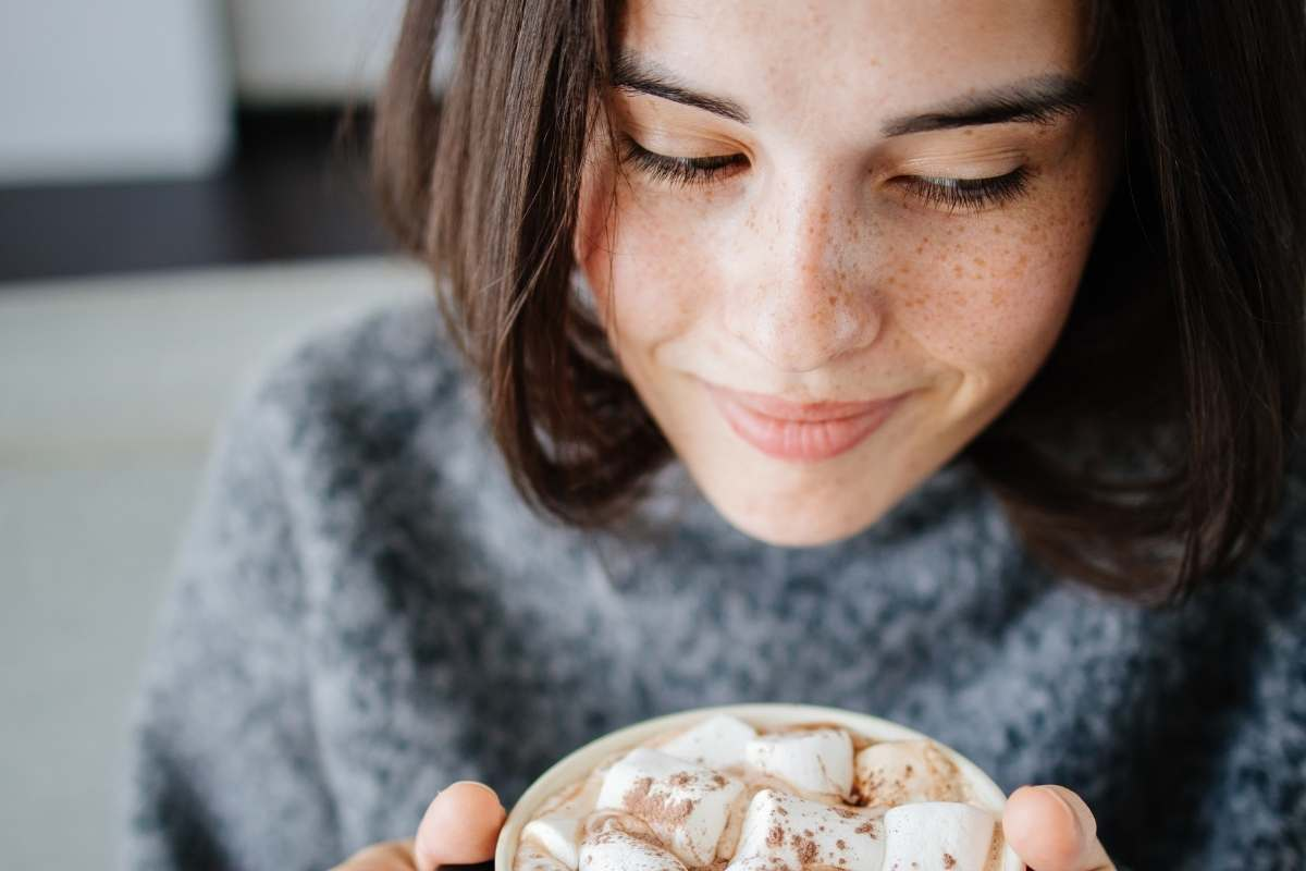 a closeup of a women with freckles smiling and drinking hot chocolate with marshmallows on top