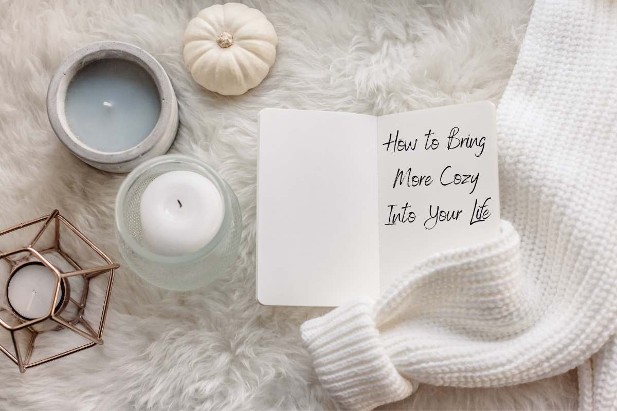 a white flatlay with a small pumpkin 3 candles a small notebook a sweater on a fur blanket