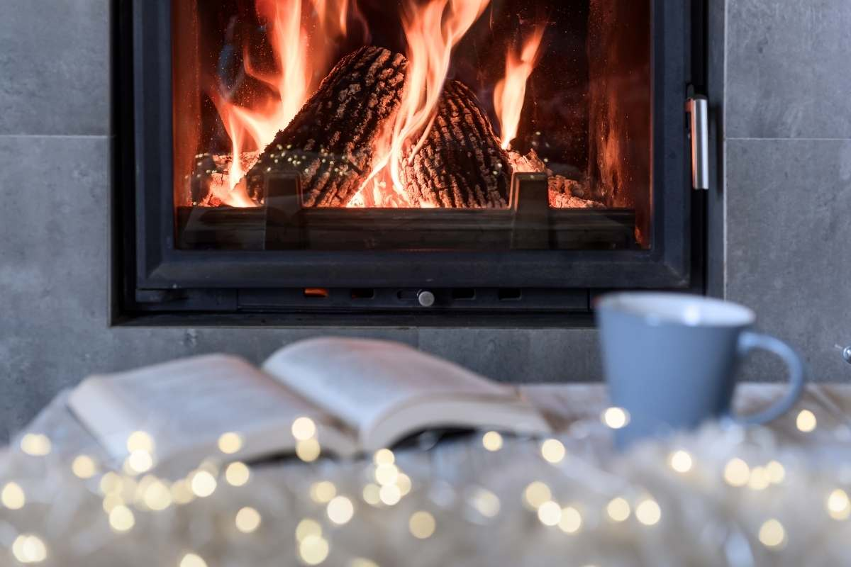 fairy lights a mug and a book laying on a table in front of a fire place