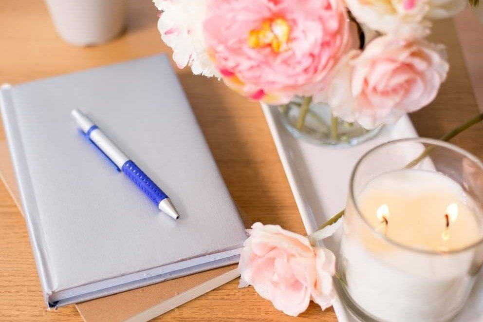 gratitude journal pen candle and pink flowers sit on a light wood table top