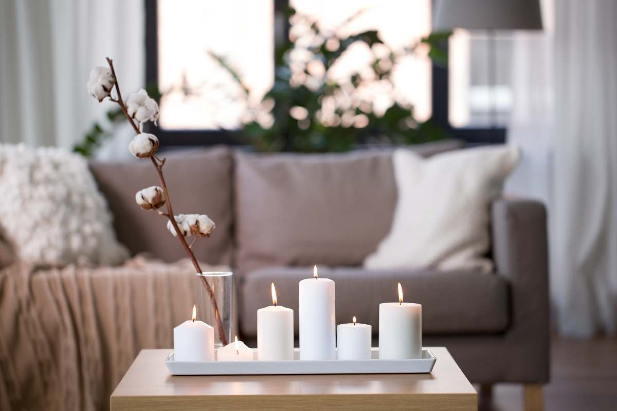 candles burning on a small table in front of a cozy sofa with pillows and a blanket all in neutral cream and white colors