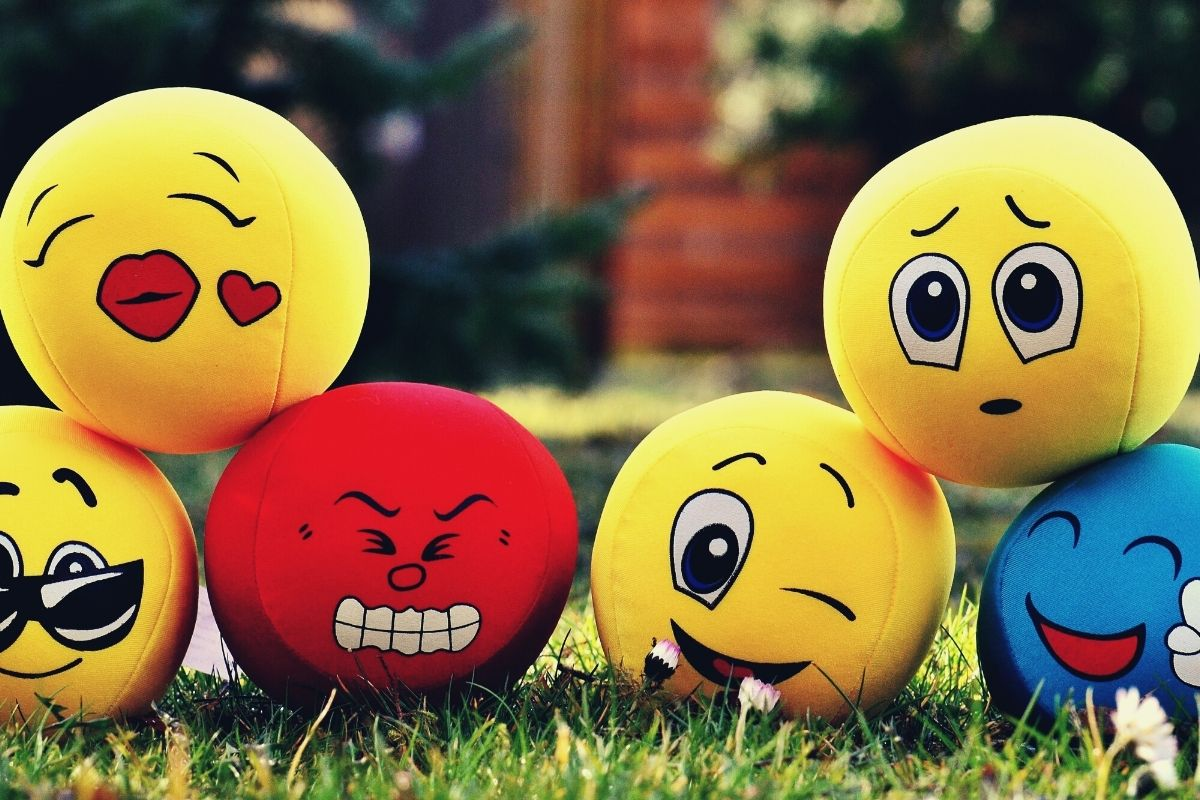 six emoji balls yellow blue and red laying in the grass to help improve happiness
