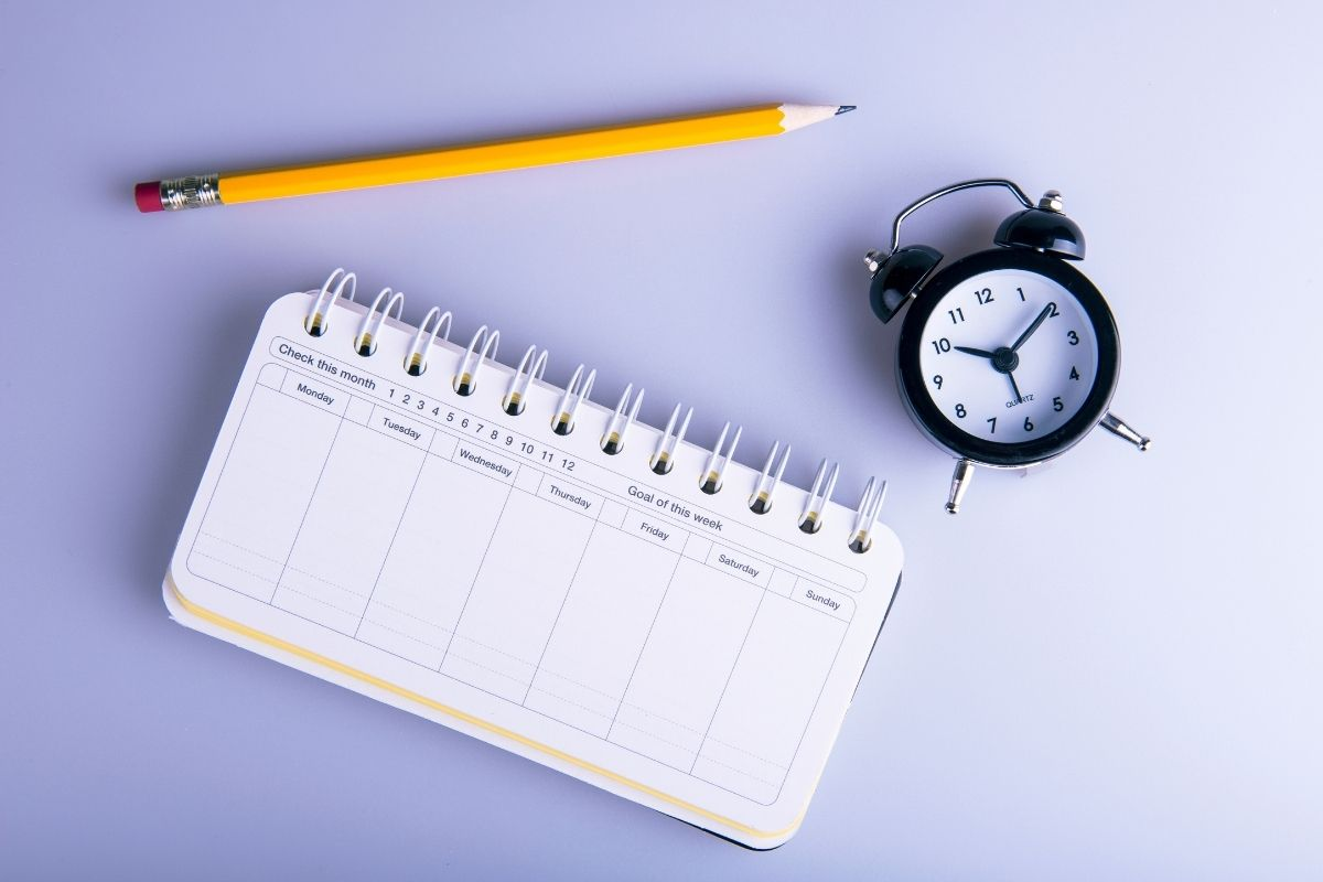 spiral notebook pencil and clock in an image to represent intentional ways to improve your happiness