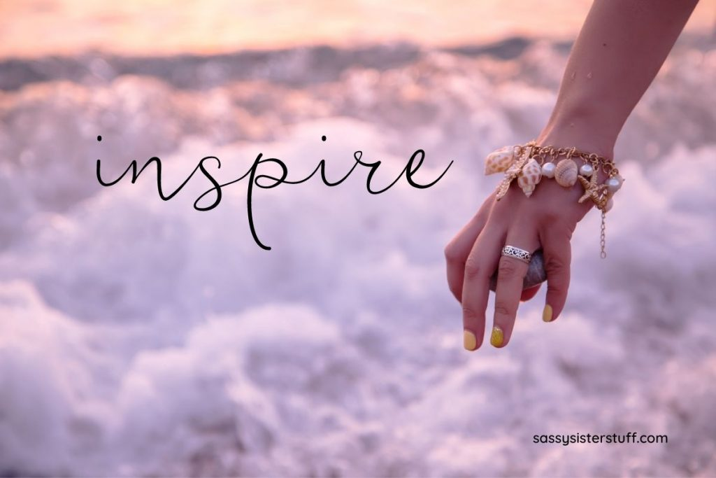 female hand with ocean charm bracelet on a cloud background with inspirational quote