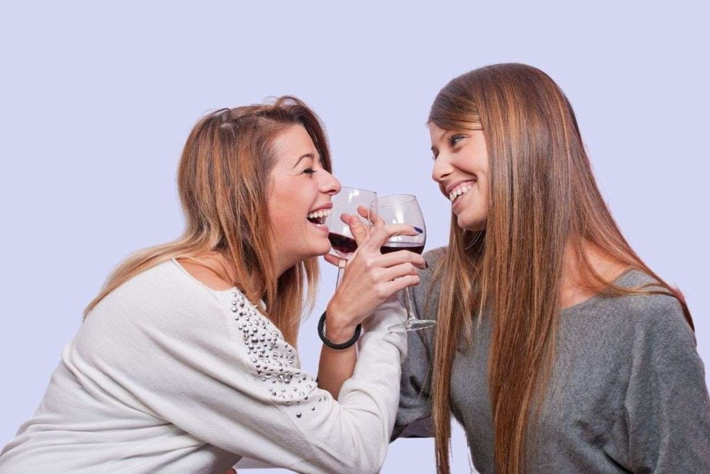 two women smiling with interlocking arms sipping on wine