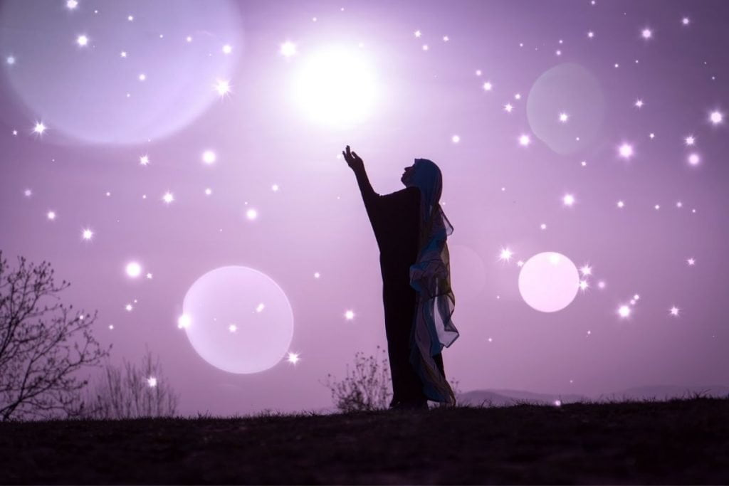 silouette of woman reaching into a skyline looking at the stars | lavender background