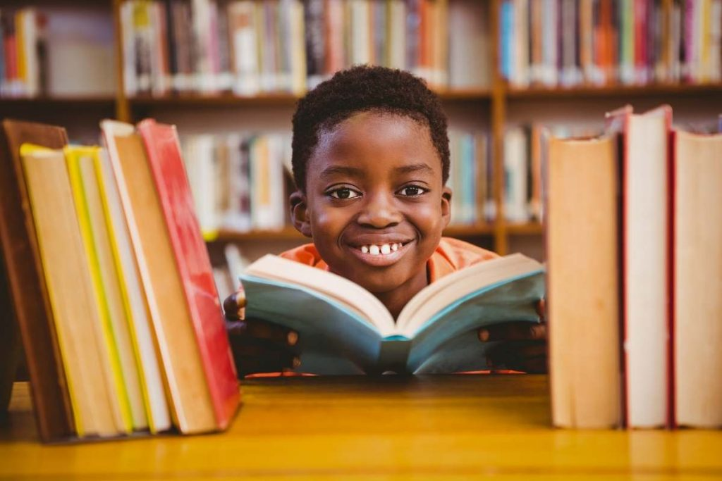 student with a big smile on his face surrounded by books