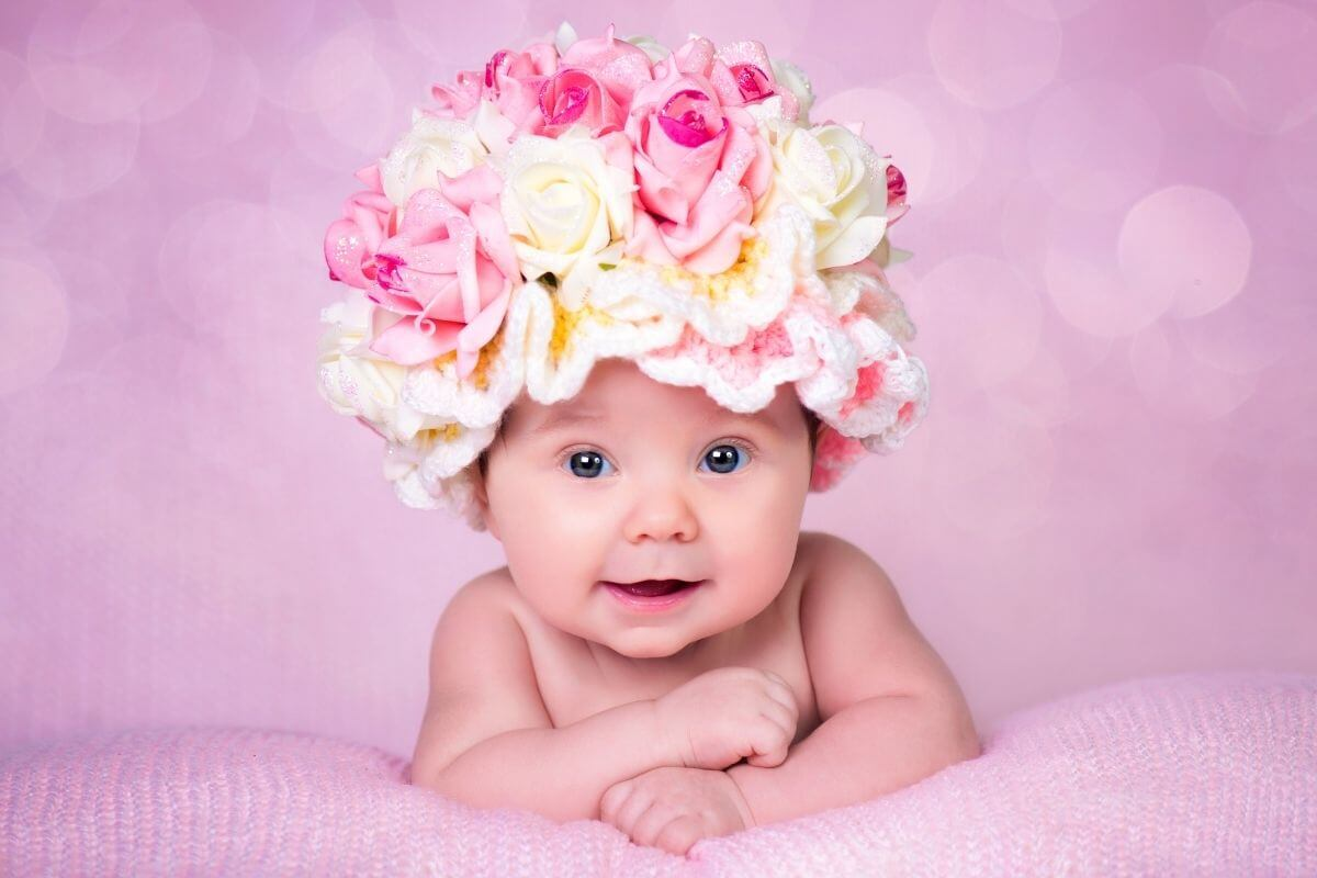 happy baby girl with big pink and white hat made of roses and crochet on a pink background and blanket