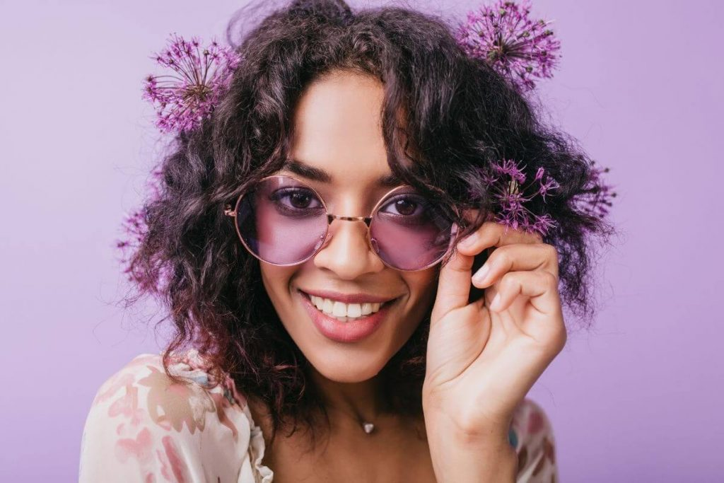happy young women with purple flowers in her haid and purple sunglasses and a lavender background