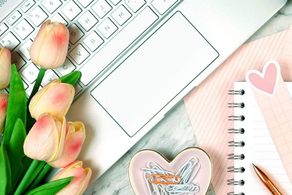 white laptop peach tulips a notebook and other desk accessories laying on a peach background