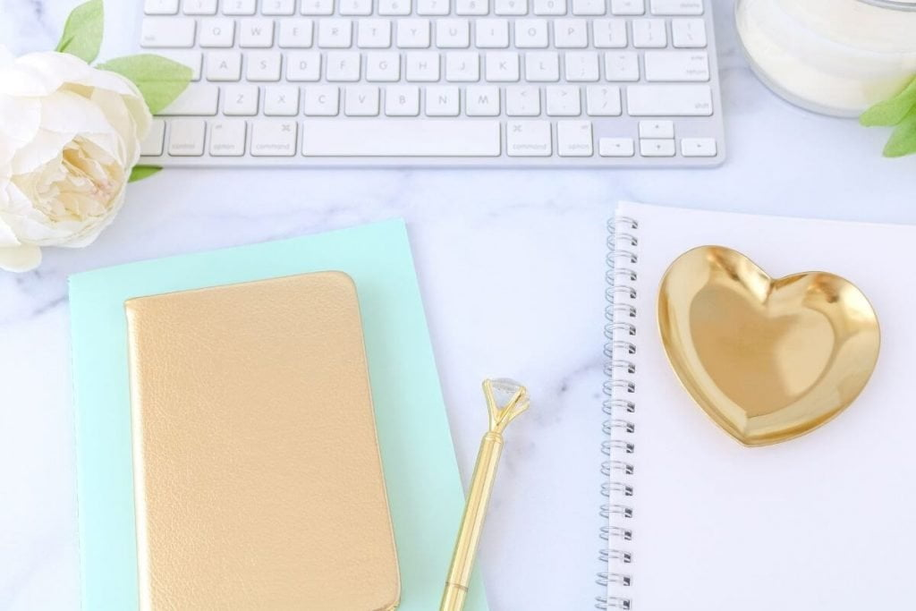 flatlay desk arrangment with keyboard journals flower pen and candle
