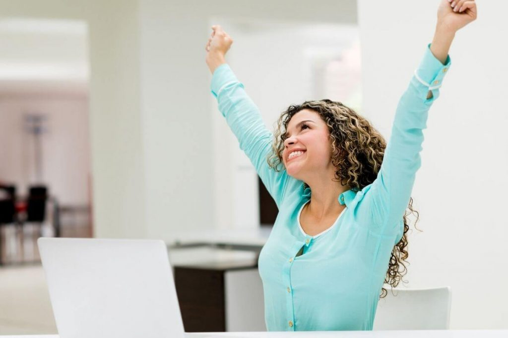 young woman reaching into the air with a beautiful smile on her face celebrating life