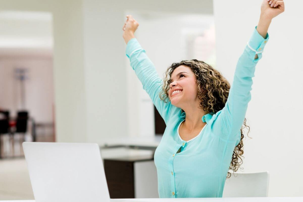 young woman reaching into the air with a beautiful smile on her face to celebrate life every day