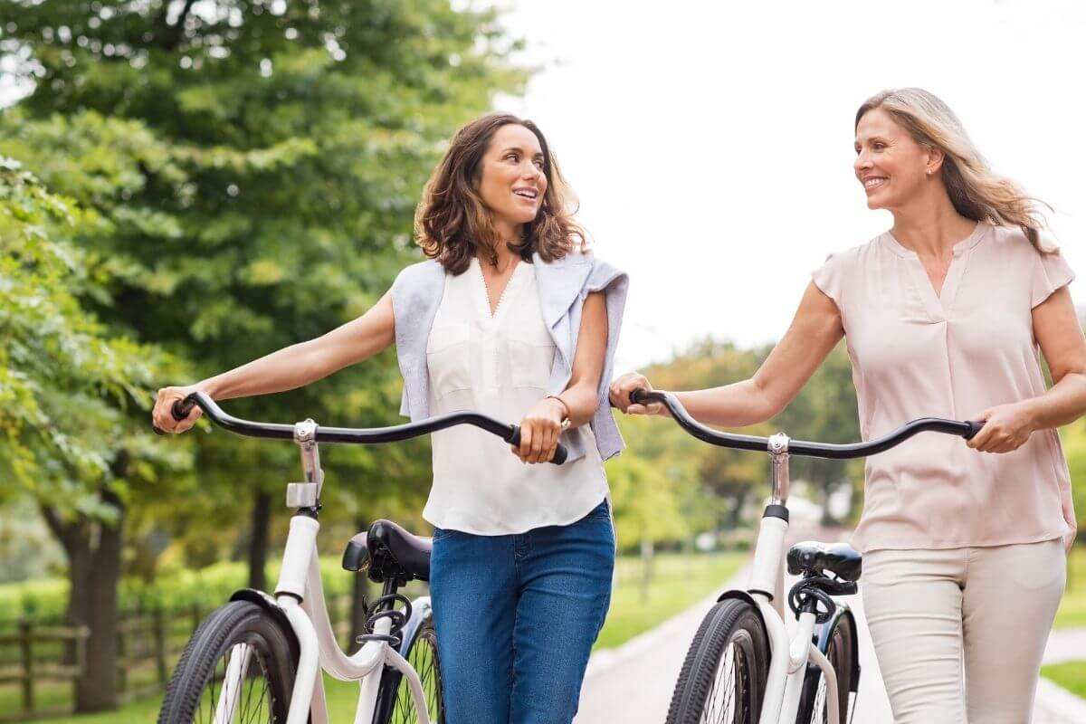 two young women walking with their bikes talking and enjoying the day outside together celebrating life