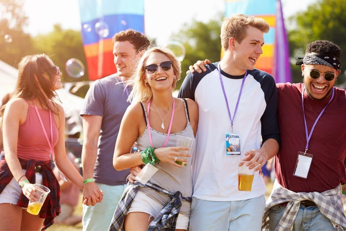 two young women and three young men having fun at a festival celebrating together