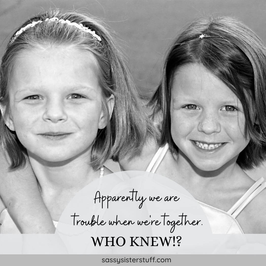 black and white photo of two little girls smiling and hugging with a funny sister quote
