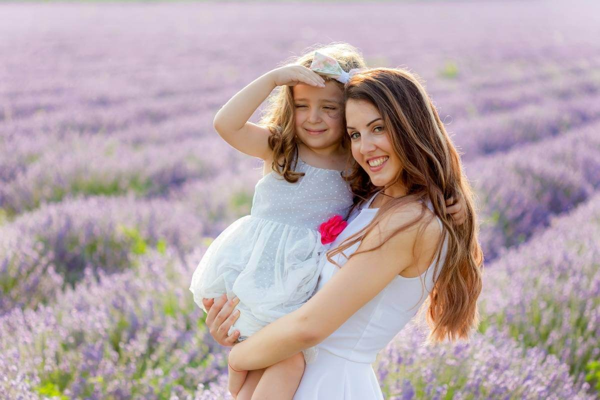 older sister holding a younger sister standing in a field of lavender flowers