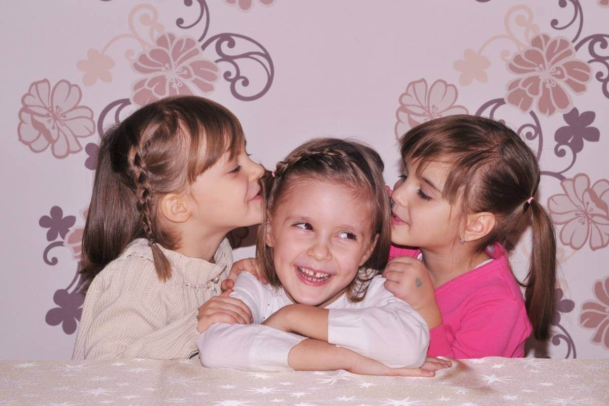 two little girls kissing the head of a third little girl who is smiling real big