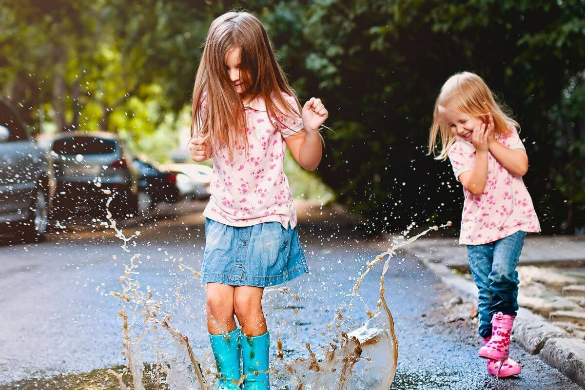 two little girl play in a puddle of water laughing and having lots of fun as they celebrate life every day